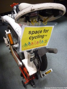 A placard attached with yellow cable ties to the seat of a (folded!) Brompton bicycle.